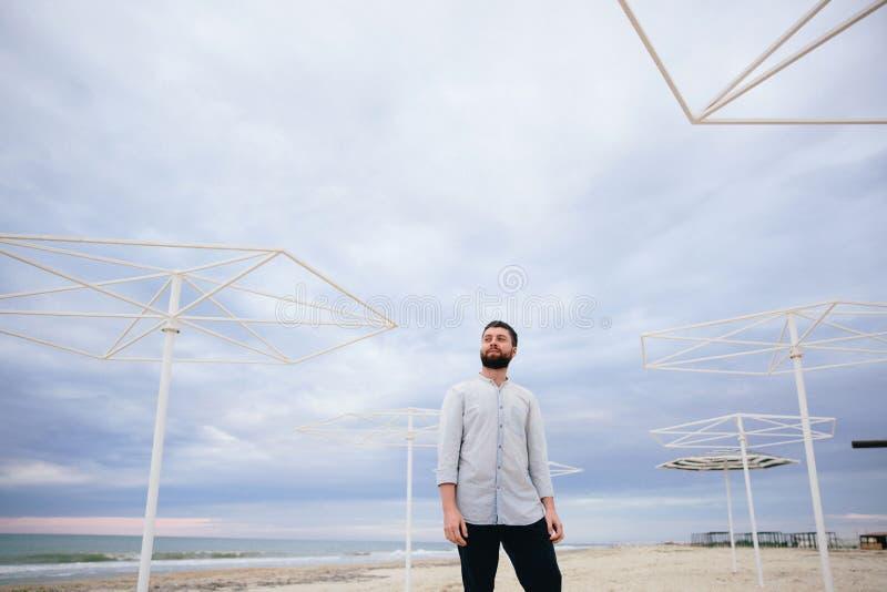 Hombre joven en una situación blanca de la camiseta en la costa contra la perspectiva de las barandillas del hierro foto de archivo