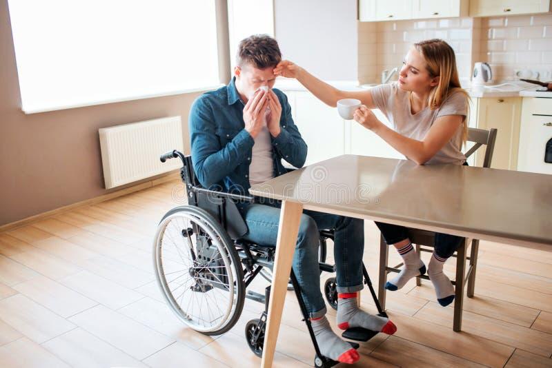 Hombre joven enfermo con necesidades e incapacidad especiales que estornuda Individuo enfermo y enfermo La mujer joven se sienta  imagen de archivo libre de regalías