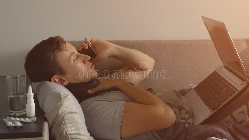 Hombre joven enfermo en la cama que trabaja en el cuaderno y que habla en el teléfono Las píldoras y las medicaciones de la abund fotografía de archivo