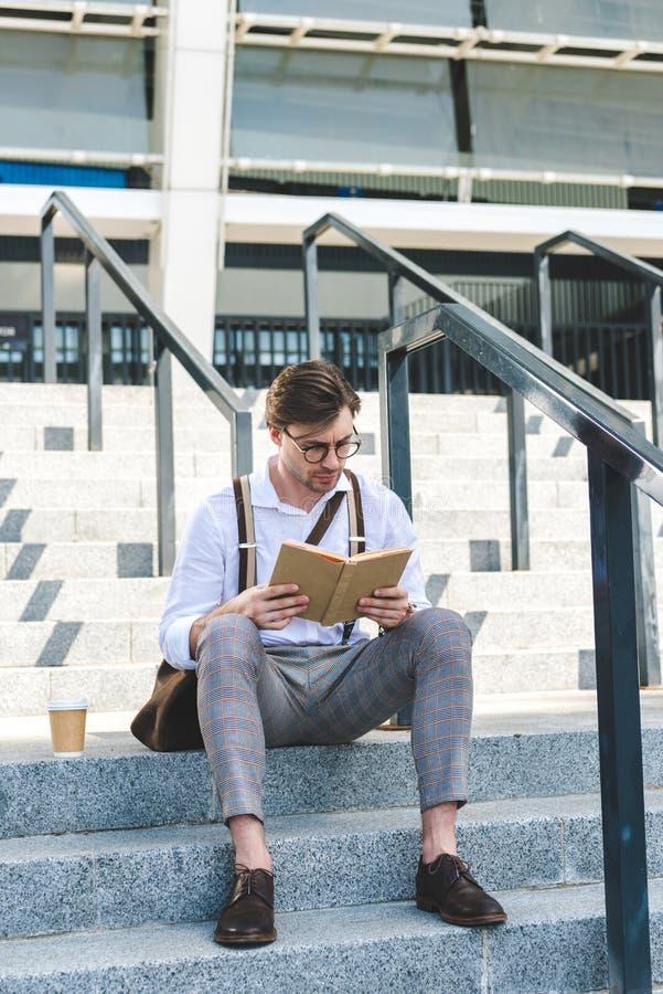 hombre joven enfocado con la taza de papel de libro de lectura del café en las escaleras fotos de archivo