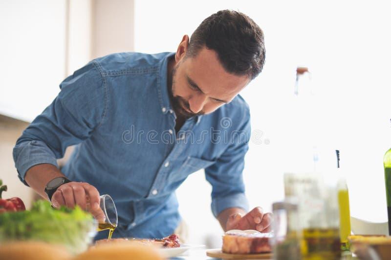 Hombre joven enfocado que cocina la carne mientras que se coloca cerca de la tabla de cocina fotografía de archivo