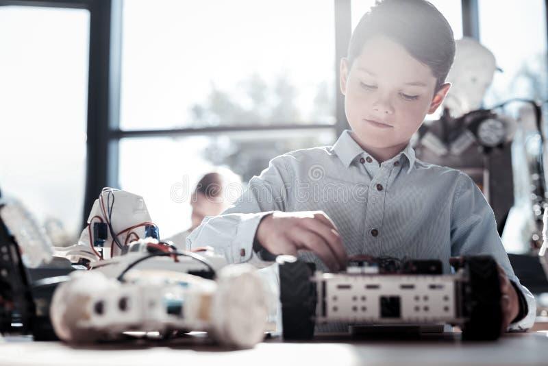 Hombre joven enfocado que construye su máquina robótica imagenes de archivo