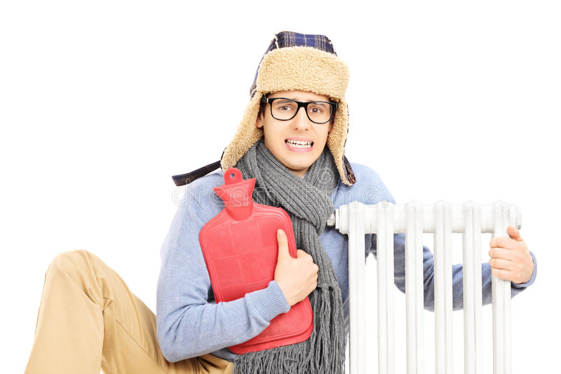 Hombre joven enfriado con la botella de agua caliente que abraza un radiador fotos de archivo