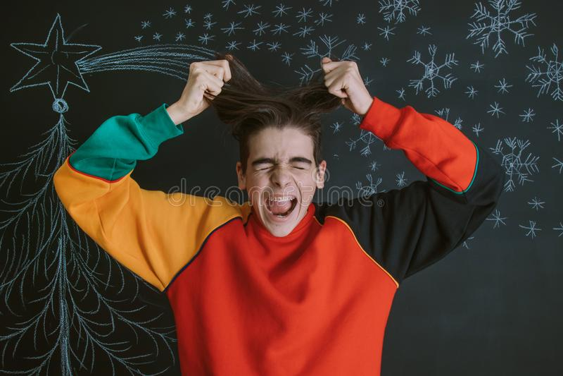 Hombre joven enojado con la Navidad imagenes de archivo