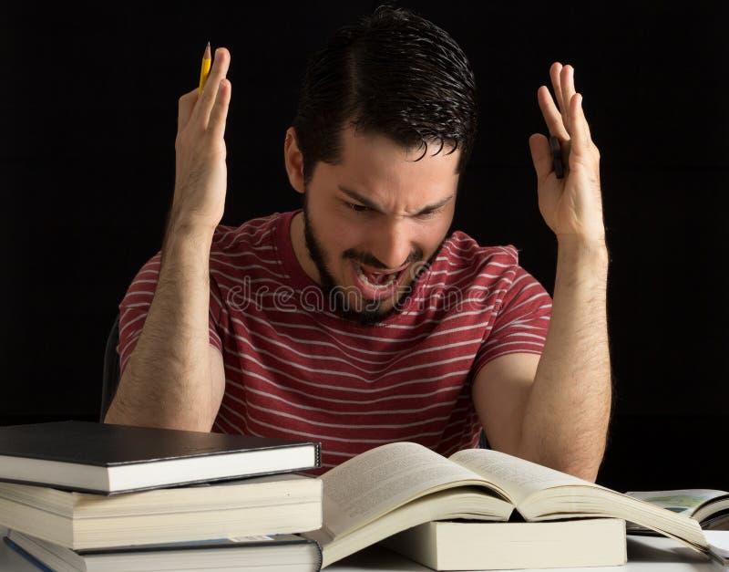 Hombre joven enojado durante estudios imagenes de archivo