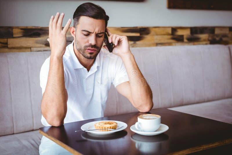 Hombre joven enojado en el teléfono imagen de archivo