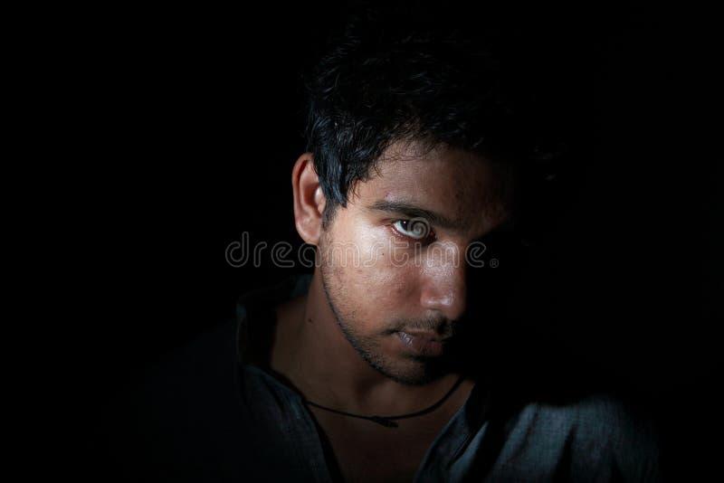 Hombre joven enojado en oscuridad imagen de archivo