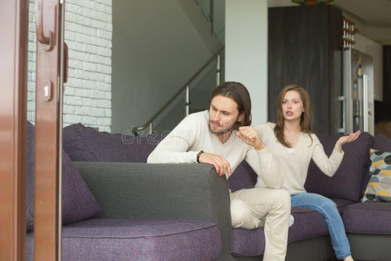 Hombre joven enojado frustrado que se sienta en el sofá que ignora discutiendo el wif fotos de archivo libres de regalías