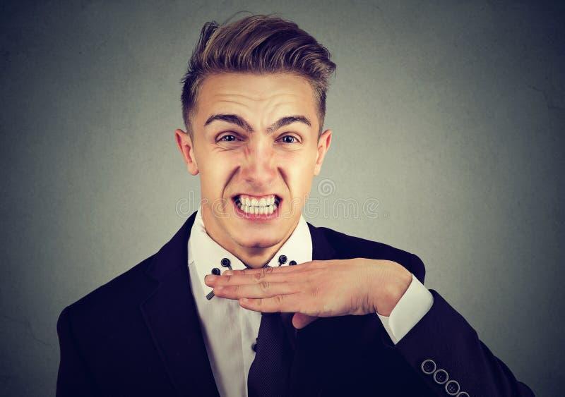 Hombre joven enojado que gesticula con la mano para parar el hablar, corte él hacia fuera foto de archivo libre de regalías