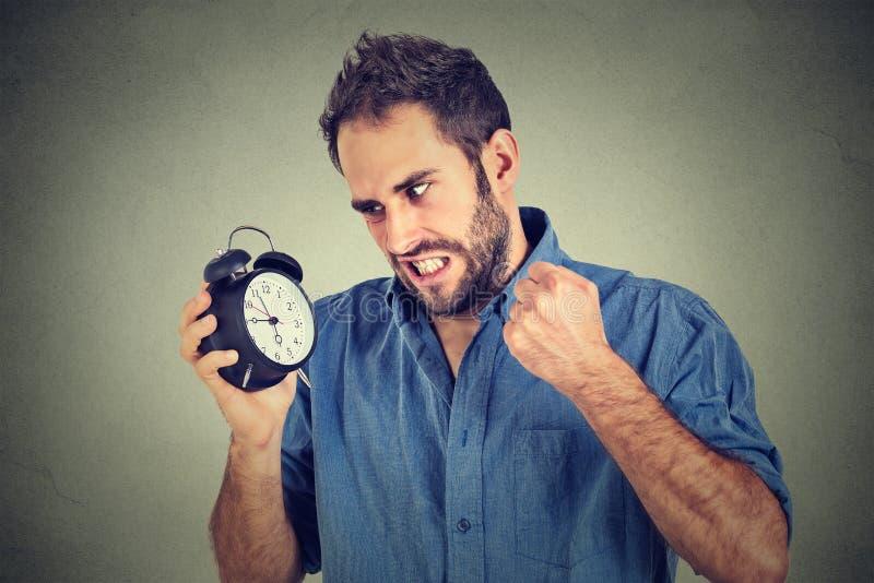Hombre joven enojado que grita en el despertador, corriendo tarde fotos de archivo
