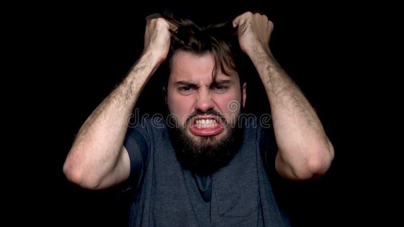 Hombre joven enojado que grita, expresando las emociones negativas, rasgando su pelo hacia fuera, aislado en fondo negro Ciérrese imagenes de archivo
