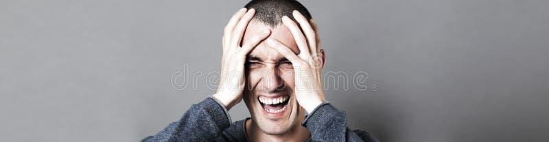 Hombre joven enojado que lleva a cabo a su cabeza, gritando su quemadura, bandera fotos de archivo libres de regalías
