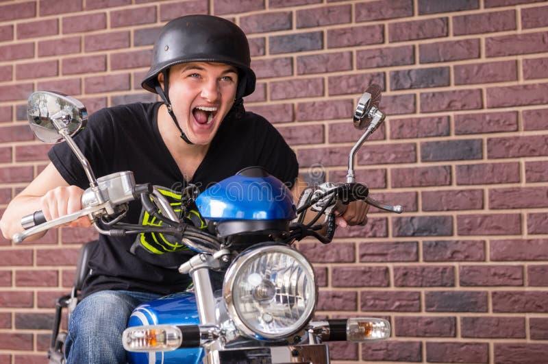 Hombre joven entusiasta que monta su moto fotografía de archivo libre de regalías
