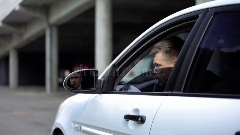 Hombre joven espiando sentado en un auto, información privada, investigación de detectives, mafia imágenes de archivo libres de regalías