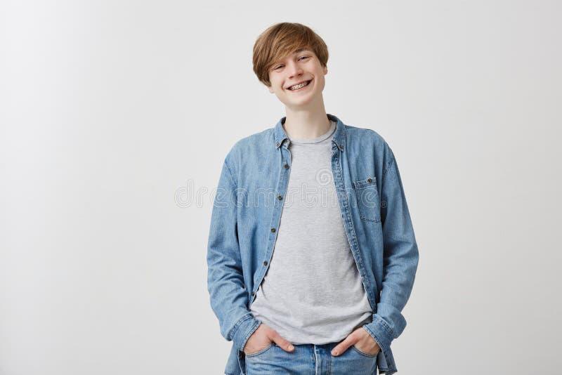 Hombre joven europeo positivo de mirada amistoso con el pelo justo y los ojos azules, sonriendo ampliamente con los apoyos, duran fotos de archivo
