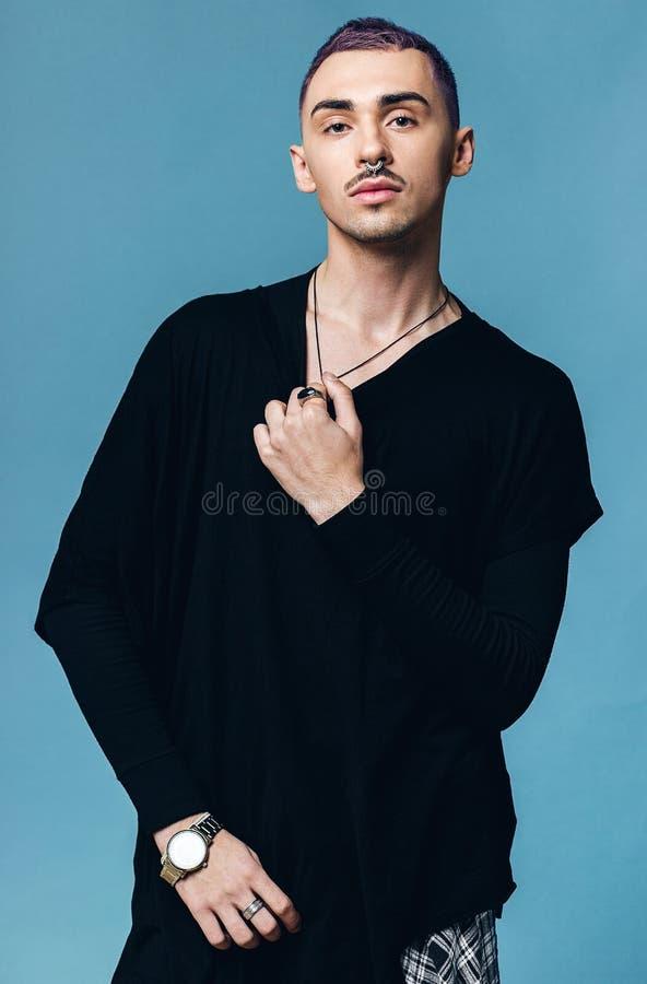 Hombre joven excepcional con el pelo púrpura en fondo azul fotos de archivo