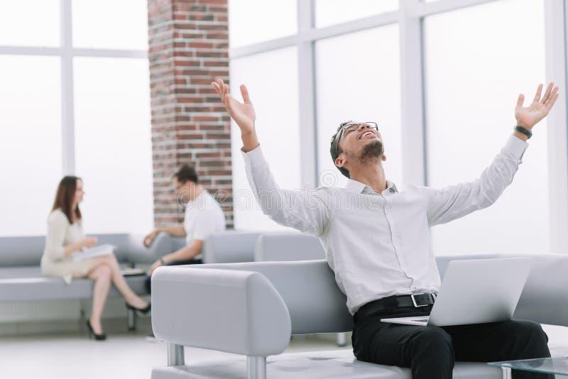 Hombre joven feliz con el ordenador portátil que se sienta en el sofá de la oficina imágenes de archivo libres de regalías