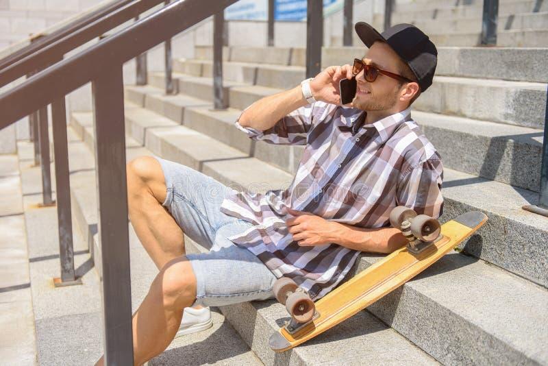 Hombre joven feliz con el patín usando smartphone imágenes de archivo libres de regalías