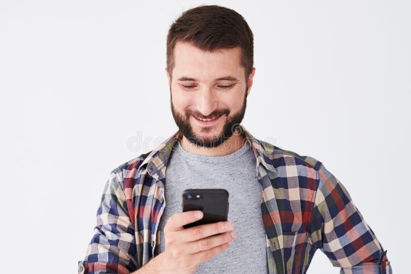 Hombre joven feliz con la barba que manda un SMS en el teléfono móvil fotos de archivo