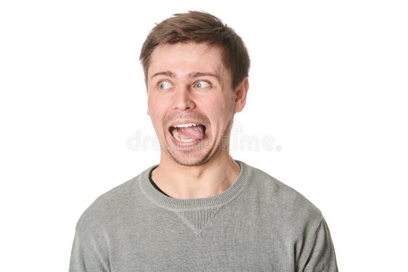 Hombre joven feliz con la expresión maníaca, en fondo gris imagen de archivo