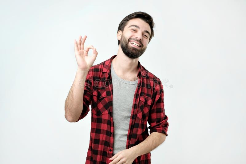 Hombre joven feliz en camisa que gesticula la muestra y la sonrisa ACEPTABLES imagen de archivo libre de regalías