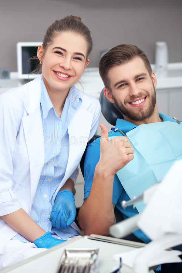 Hombre joven feliz en el donante de la silla de un dentista pulgares para arriba fotografía de archivo