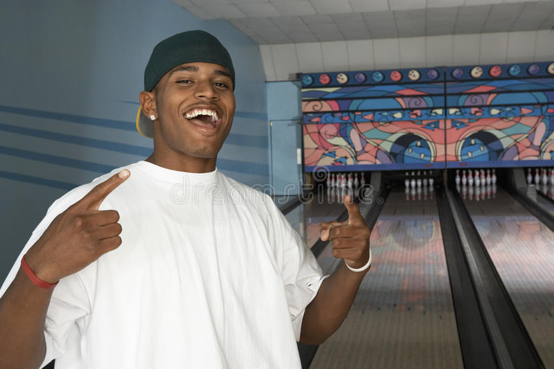 Hombre joven feliz en la bolera imagen de archivo