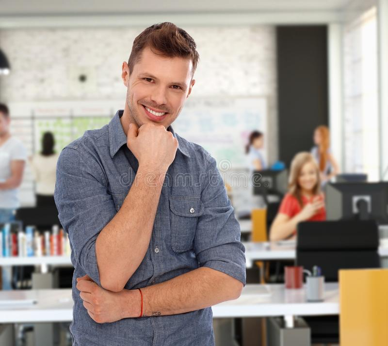 Hombre joven feliz en la oficina joven de moda fotos de archivo