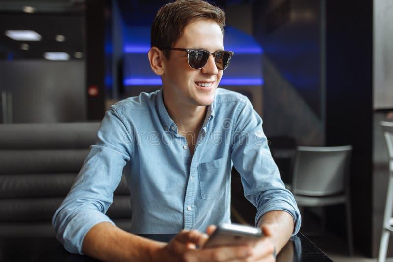Hombre joven feliz en los vidrios, con el teléfono a disposición, sentándose en el café, conveniente para hacer publicidad, inser foto de archivo