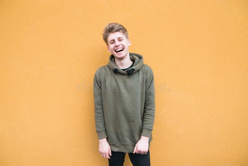 Hombre joven feliz en soportes de la ropa casual en el fondo de una pared anaranjada y de sonrisas fotos de archivo libres de regalías