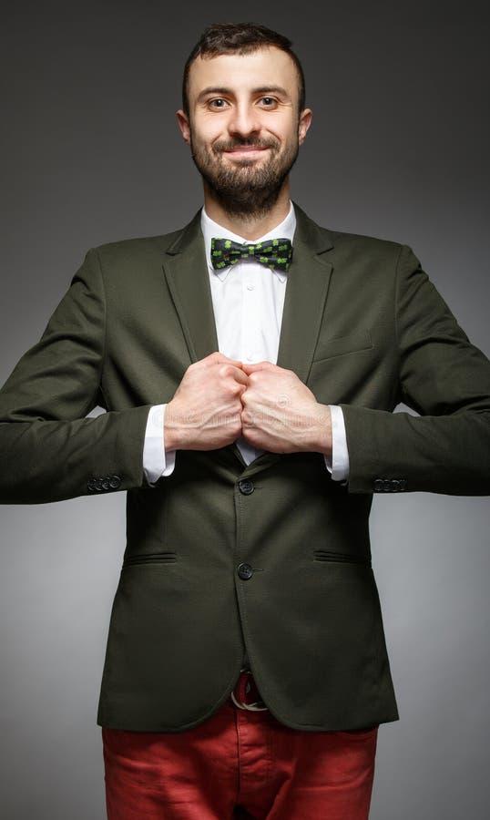 Hombre joven feliz en un traje verde foto de archivo