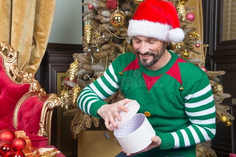 Hombre joven feliz que abre la caja de regalo y que sonríe alegre fotos de archivo libres de regalías