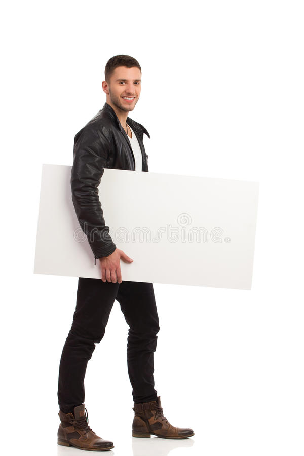 Hombre joven feliz que camina con la bandera en blanco. imagenes de archivo