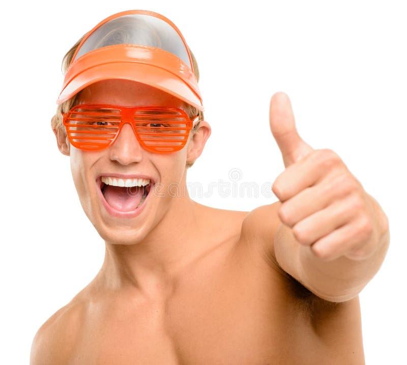 Hombre joven feliz que celebra la sonrisa de los pulgares para arriba aislada en la parte posterior del blanco imagen de archivo