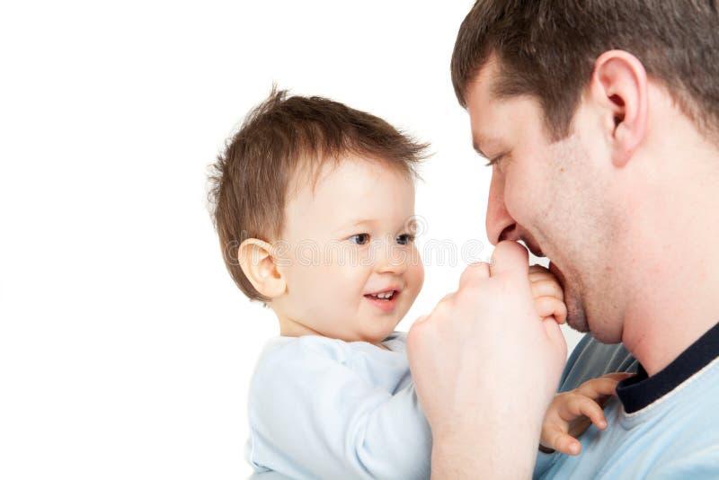 Hombre joven feliz que detiene a un bebé sonriente, aislado. Padre e hijo imagen de archivo libre de regalías