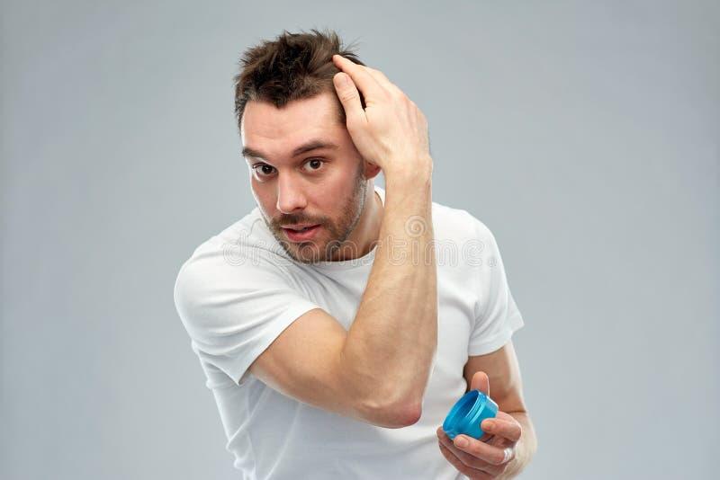 Hombre joven feliz que diseña su pelo con la cera o el gel imagen de archivo libre de regalías