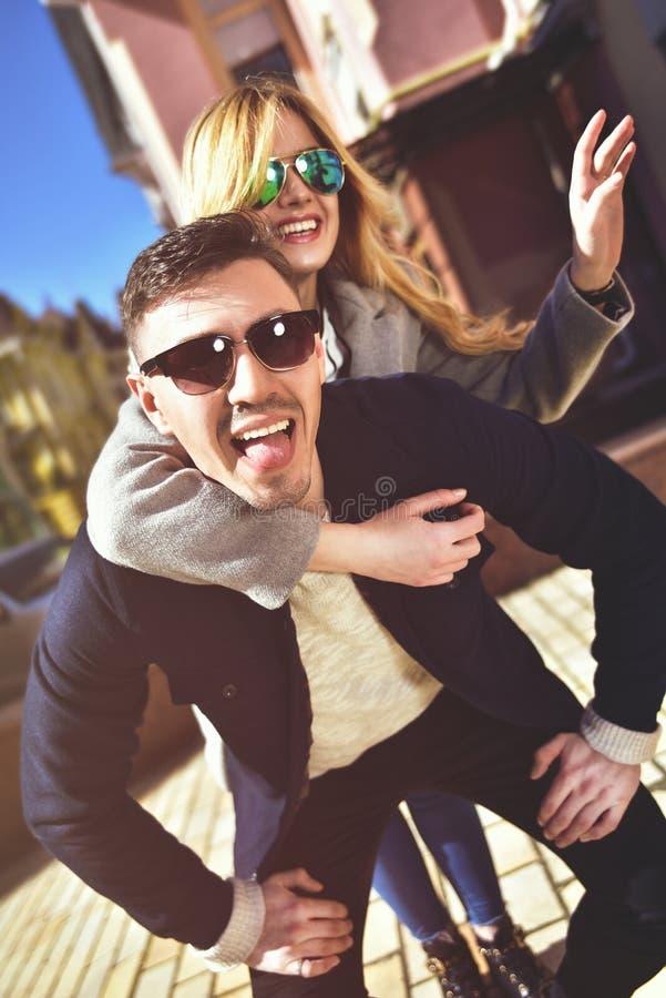 Hombre joven feliz que lleva a cuestas a su novia foto de archivo libre de regalías