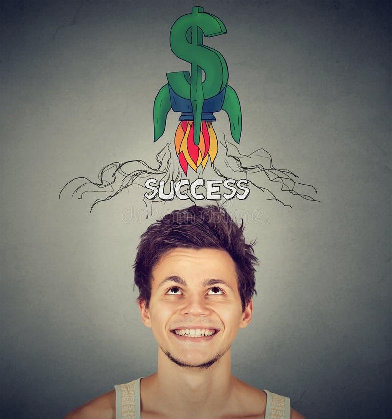 Hombre joven feliz que mira para arriba con la muestra de dólar del cohete sobre la cabeza fotos de archivo