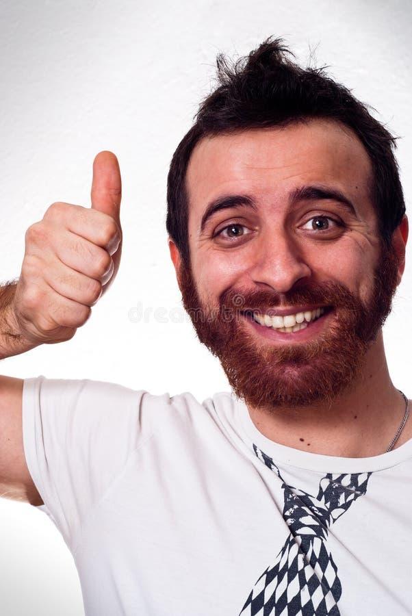 Hombre joven feliz que muestra el pulgar encima de la muestra fotografía de archivo libre de regalías