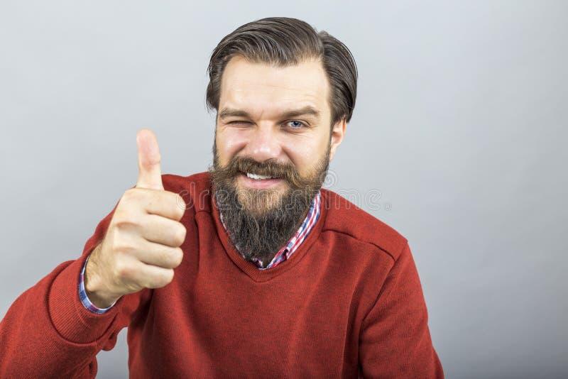 Hombre joven feliz que muestra la muestra ACEPTABLE con su pulgar para arriba y el centelleo imágenes de archivo libres de regalías