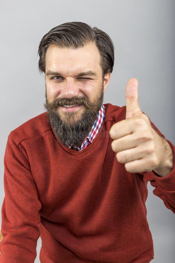 Hombre joven feliz que muestra la muestra ACEPTABLE con su pulgar para arriba y el centelleo fotos de archivo libres de regalías