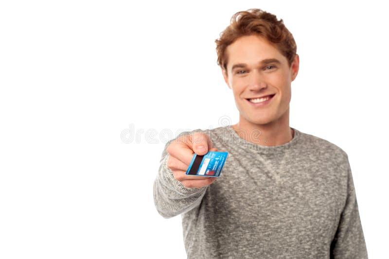 Hombre joven feliz que muestra la tarjeta de crédito imagen de archivo libre de regalías