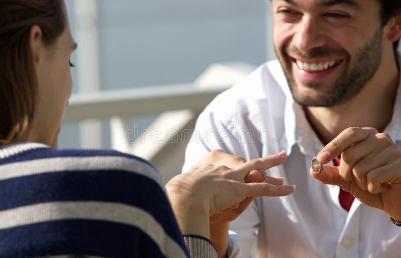 Hombre joven feliz que propone boda a la mujer con el anillo de compromiso imágenes de archivo libres de regalías