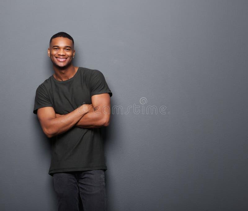 Hombre joven feliz que se coloca con los brazos cruzados fotos de archivo libres de regalías