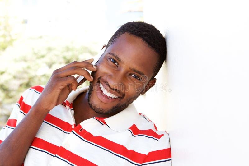 Hombre joven feliz que se inclina para emparedar y que habla en el teléfono celular foto de archivo