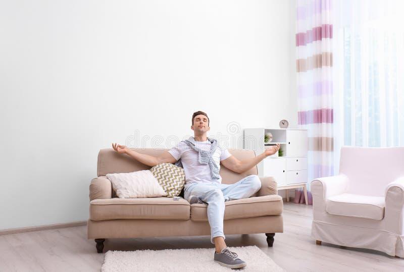 Hombre joven feliz que se sienta debajo del acondicionador de aire fotografía de archivo libre de regalías