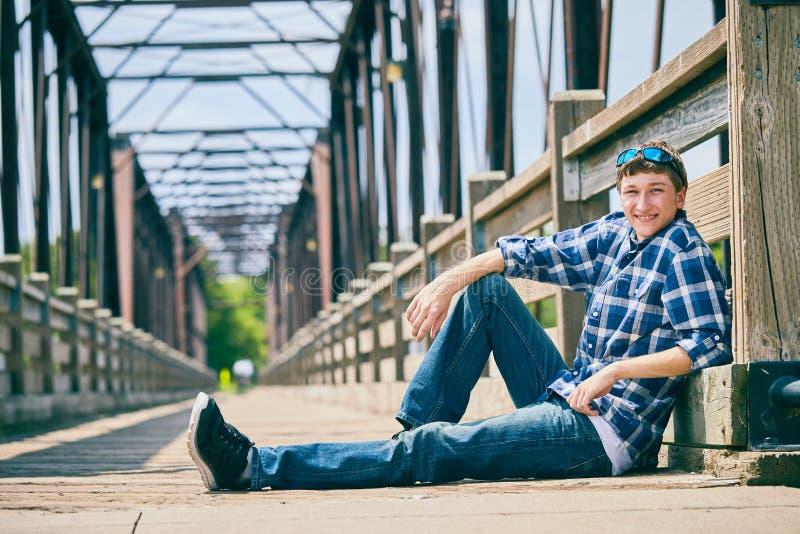 Hombre joven feliz que se sienta en el puente de madera fotos de archivo