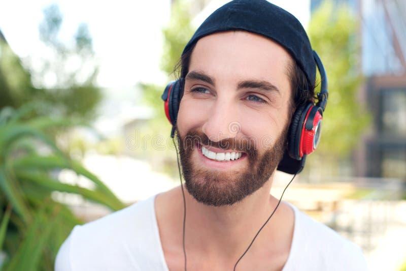 Hombre joven feliz que sonríe con los auriculares al aire libre imágenes de archivo libres de regalías