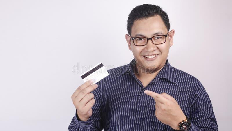 Hombre joven feliz que sonríe y que señala la tarjeta de crédito fotografía de archivo libre de regalías