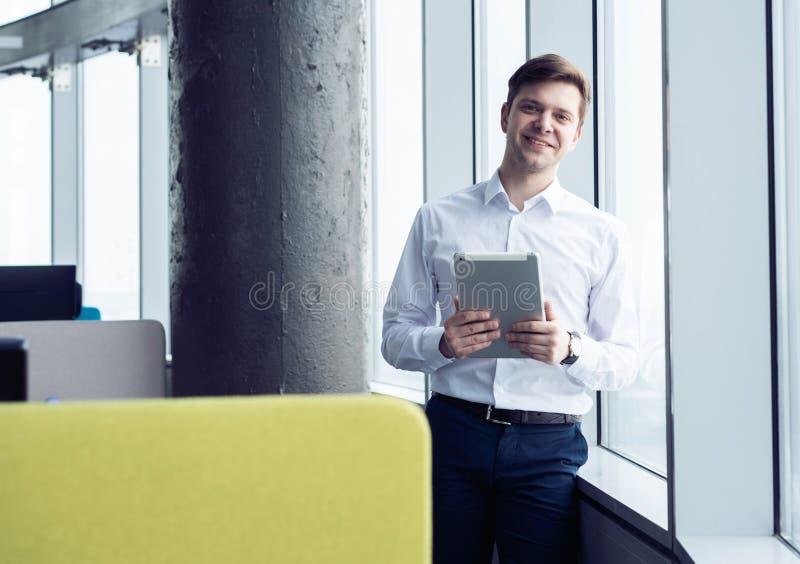 Hombre joven feliz que sonr?e en la c?mara con una tableta en su mano foto de archivo